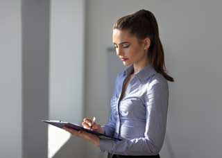 Woman making notes on a clipboard