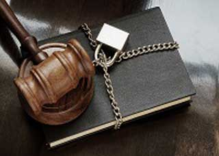 Image of a padlocked chain wrapped around a legal book with a gavel