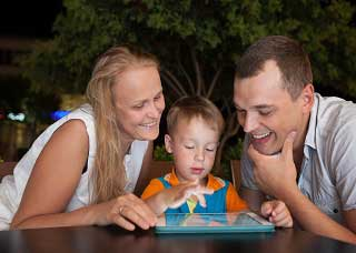 Image of a woman, man, and boy interacting over a tablet