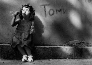 Black and white photo of a girl blowing bubbles while sitting on a curb