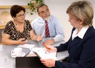 Image of two older individuals meeting with an attorney