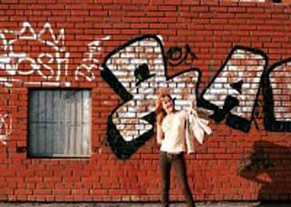 Image of a teen standing in front of graffiti